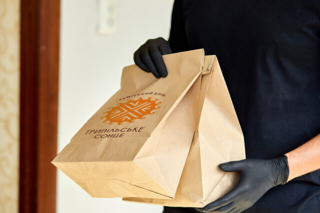 Courier in black hold go box food, delivery service, Takeaway restaurants food delivery to home door. Stay at home safe lives from coronavirus COVID-19 outbreak. Contactless delivery service under quarantine.